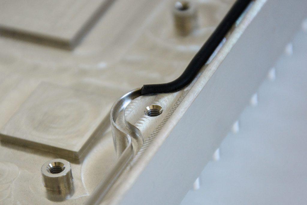 Dichtschnur, die in eine umlaufende, kleine Auskerbung eines Gehäuseteils aus Aluminium eingepresst ist.