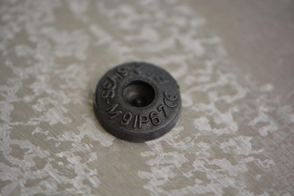 """Kleine, runde Dichtungstülle aus schwarzem Kunststoff mit Aufschrift: """"M9IP67"""""""